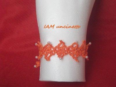 Braccialetto in cotone arancione lavorato a rombi all'uncinetto con perline
