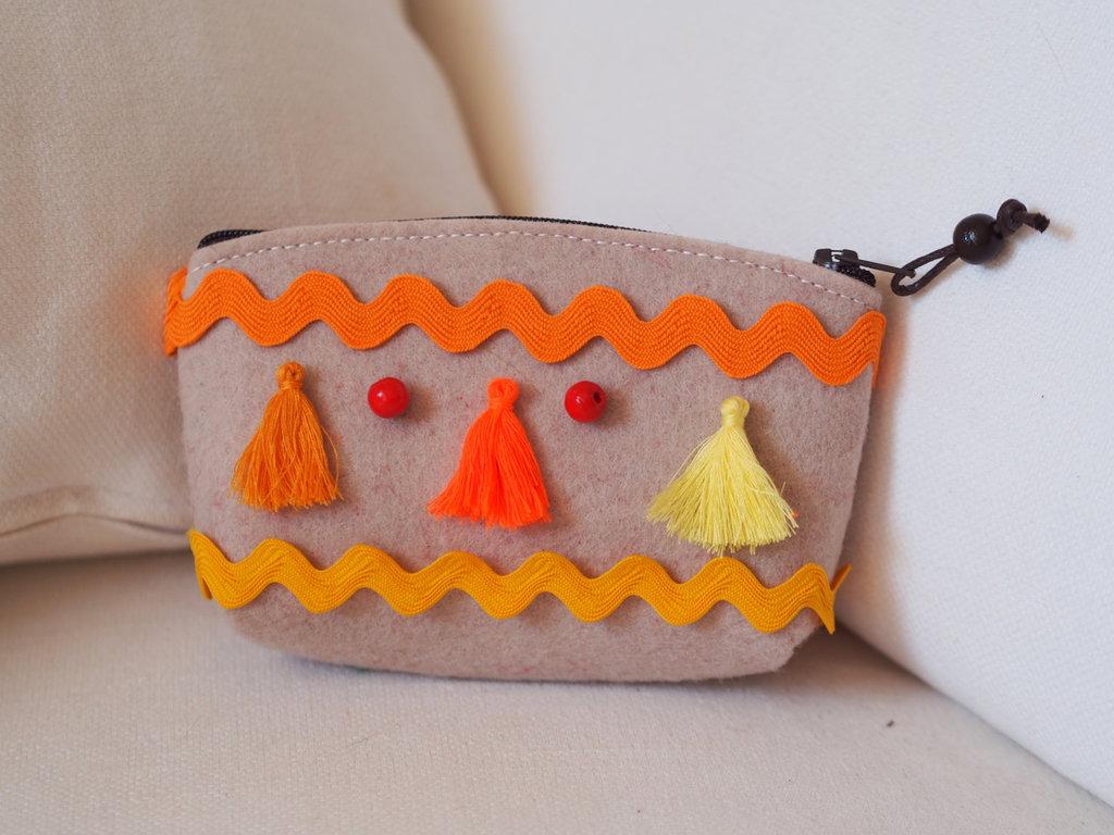 Pochette in feltro beige con nappine,passamaneria e perle rosse in legno.Toni del giallo,arancione,arancione squillante