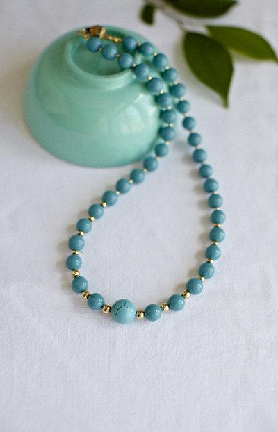 Collana corta con perle turchesi e perline dorate.