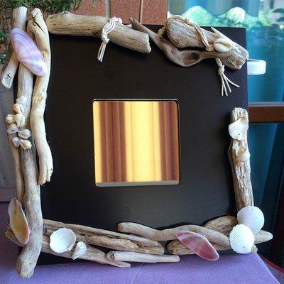 specchio con legni e conchiglie