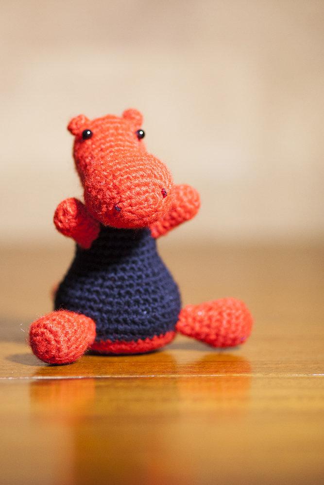 Pupazzo a forma di drago realizzato in lana acrilica all'uncinetto con la tecnica amigurumi, nei colori rosso e nero.