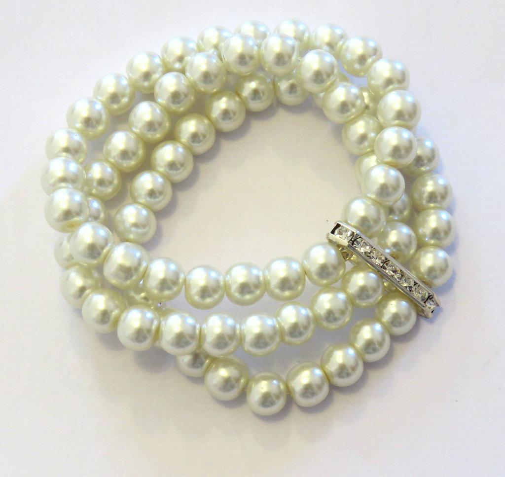 Bracciale elastico di perle color panna a tre fili con distanziatore argentato e strass
