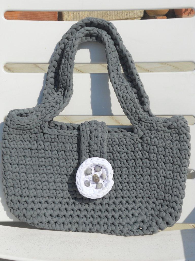 Borsa sottobraccio realizzata all'uncinetto in fettuccia di lycra colore grigio con bottone bianco artigianale con applicazione di conchiglie