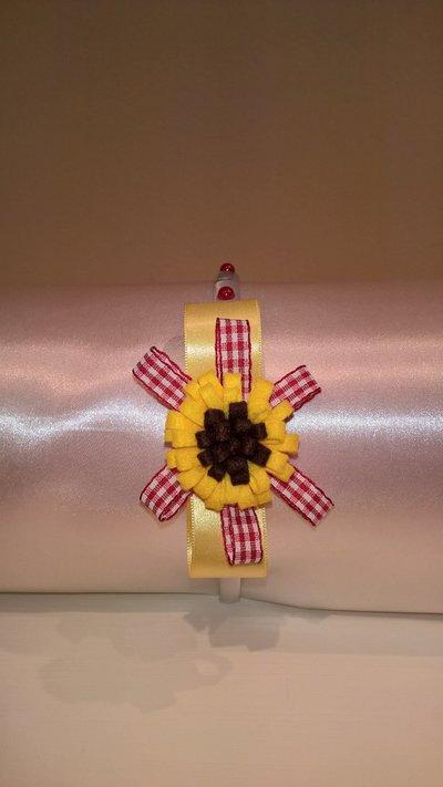 Cerchietto per capelli decorato con fiore di feltro a girasole, nastri e strass.