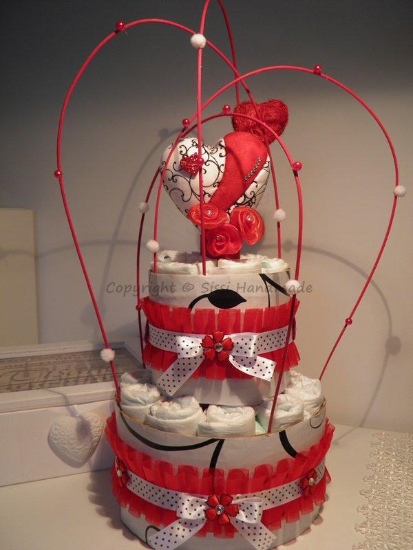 Torta di pannolini bianca con decorazioni floreali nere e rosse e cuore in patchwork