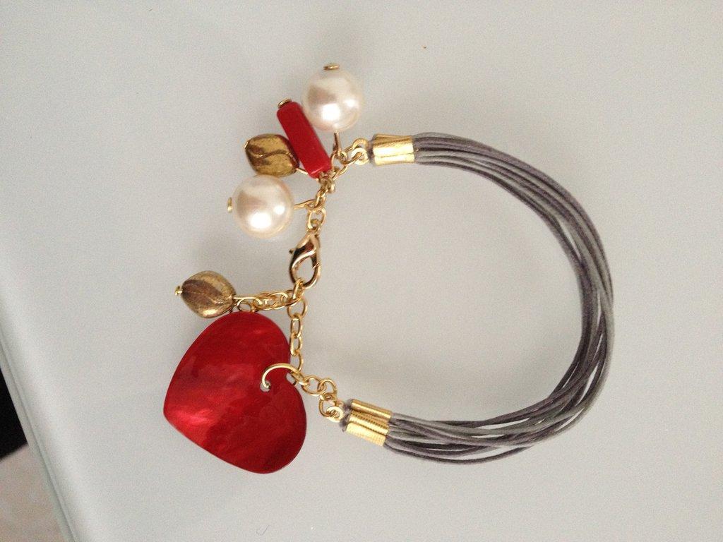 braccialetto fatto a mano grigio in alcantara, con pendenti oro, rossi, perle bianche, in vetro e un pendente cuore rosso madreperlato