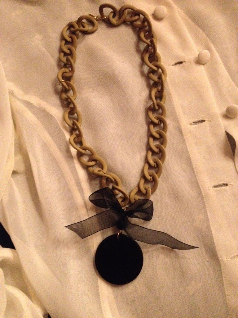 Collana fatta a mano molto simpatica, in maglia di resina con ciondolo nero tondo in resina e fiocco in tessuto voile. Nella sua semplicità risulta sicuramente chic.