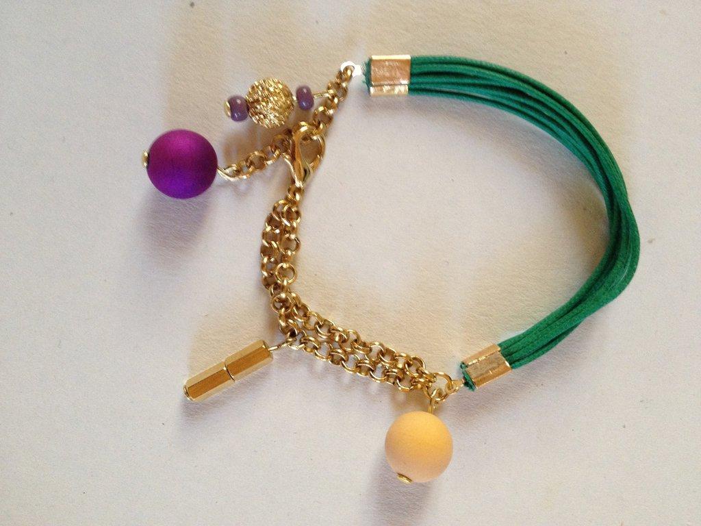 Braccialetto fatto a mano verde brillante in alcantara e maglia in metallo oro/rame, con pendenti oro, viola e gialli. Sfiziosissimo.