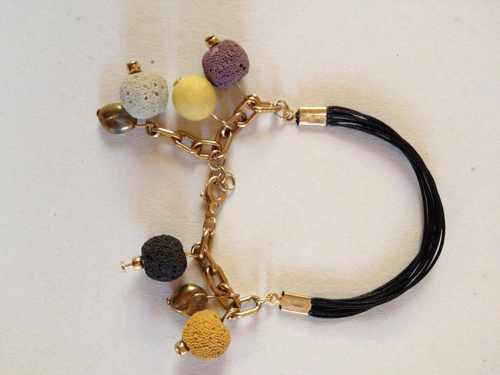 Braccialetto fatto a mano nero in alcantara e maglia in metallo colore oro/rame, con pendenti neri, gialli, beige e marroni in pietra lavica, resina e vetro. Sfiziosissimo