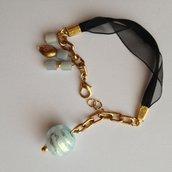 Braccialetto fatto a mano nero in tessuto voile e maglia metallo colore oro, con pendenti in vetro azzurro. Delizioso