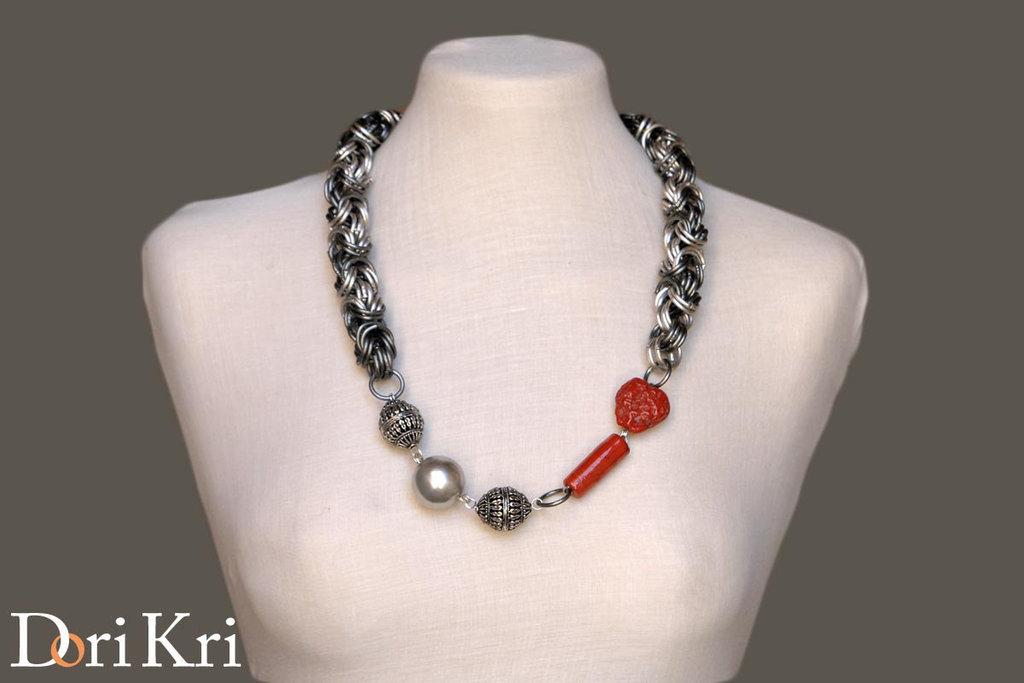 Collana a catena grossa assimetrica argentata, opaca, con cuore in ceramica rossa.