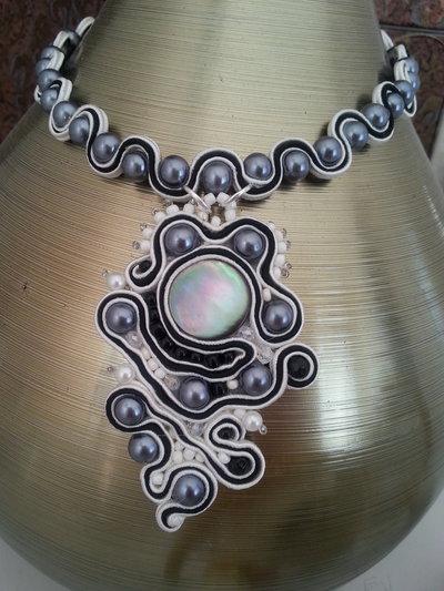 Collana elegante con le perline grige e bianche eseguita in tecnica soutache