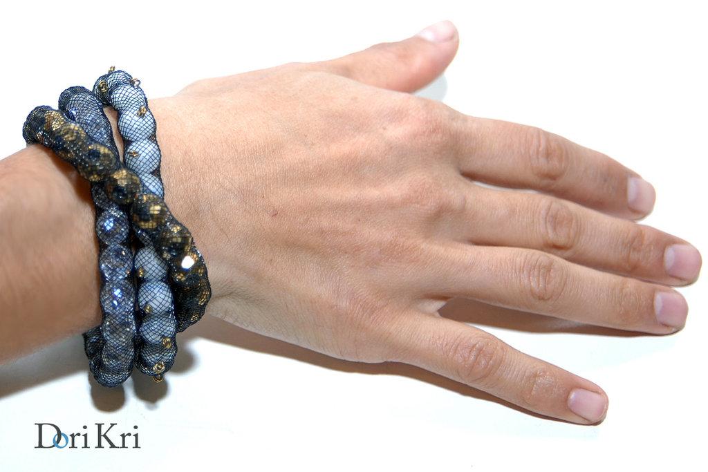 """Braccialetto fatto di titanio """"farciti"""" con delle perle di vetro di diversi colori: bianco, bronzo e trasparente brillante"""