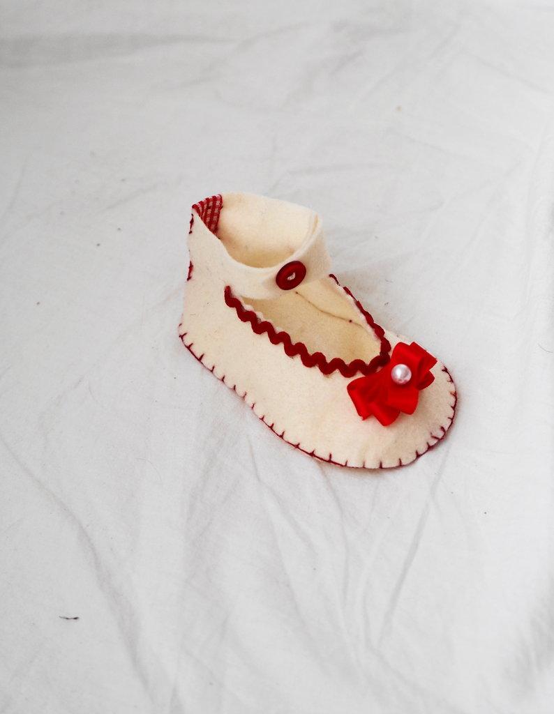 Scarpa hand made (feltro crema) da bambina.DECORAZIONE NATALIZIA.Decorata con passamaneria,nastro,coccarda in raso con perla,bottone.