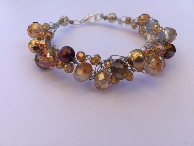 Bracciale fatto a mano con fili argento, cristalli e perline color terra e giallo/oro