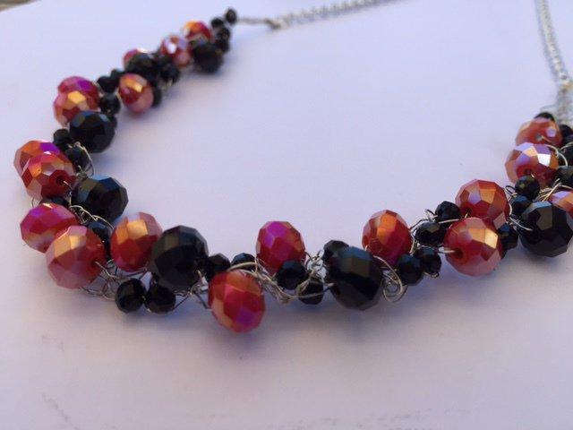 Collana realizzata a mano con fili argento, cristalli neri e rossi
