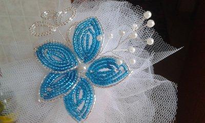 Fiore di perline azzurre e argento con pom pom in tulle.