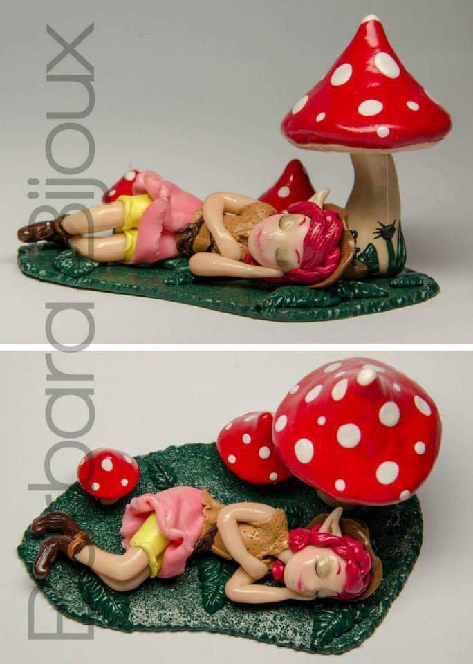 Statuetta con dolce elfa che riposa vicino i funghetti.