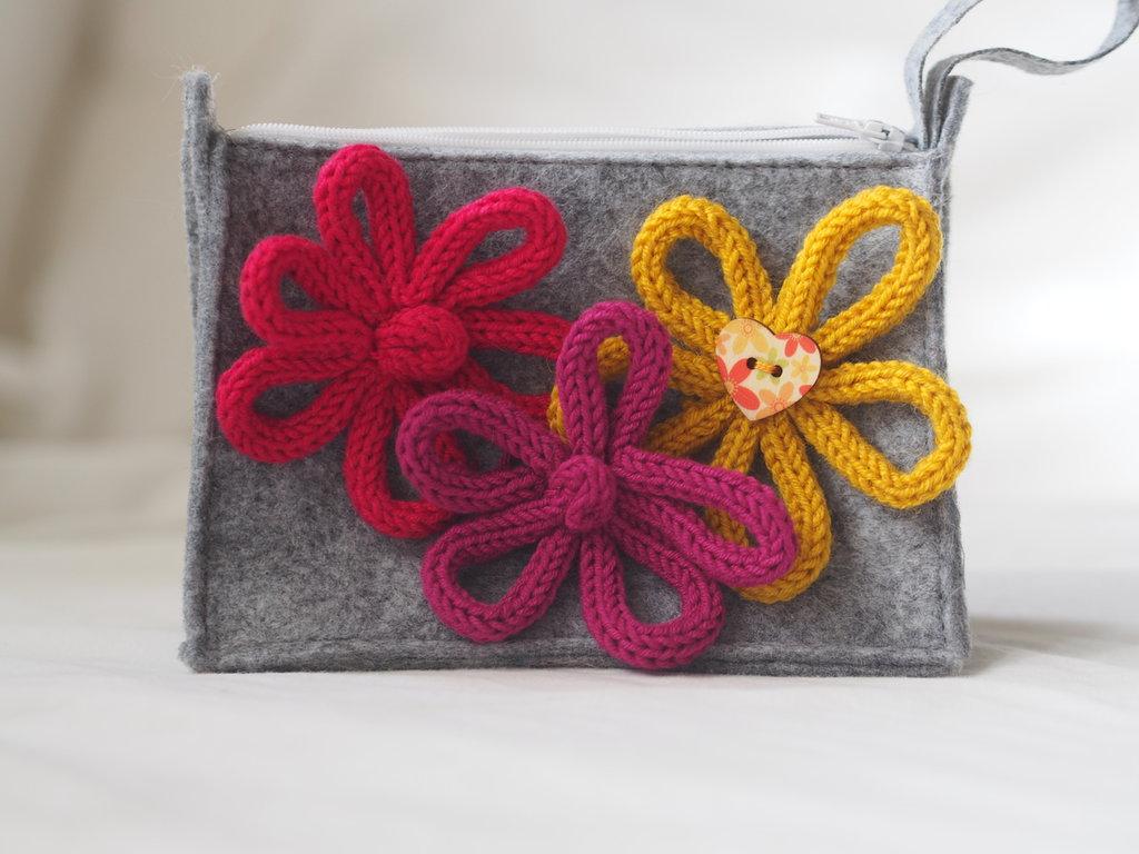 Pochette in feltro grigio chiaro.Porta trucco,gioielli.Accessorio da borsetta.Decorata con 3 fiori maglia tubolare (tricotin) e bottone
