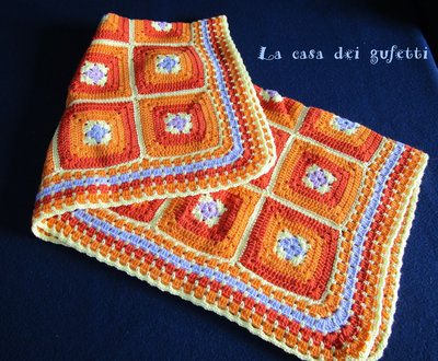Copertina all'uncinetto per passeggino composta da mattonelle arancio gialle e azzurre