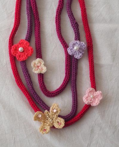 COLLANA in maglia di lana(tricotin) 3 fili.Applicazione di 4 fiori uncinetto e 1 farfalla.Strass,perline,perle.Toni del viola.Diversi colori