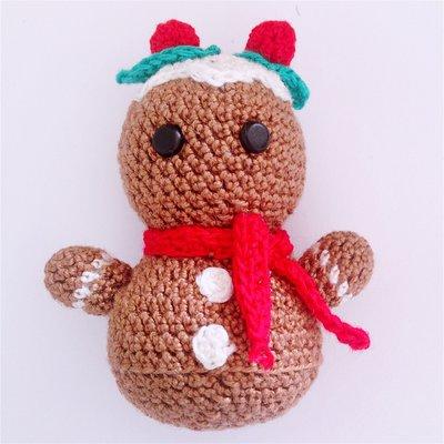 Biscottino di zenzero amigurumi marrone, con glassa e foglioline di agrifoglio di Natale, fatto a mano all'uncinetto