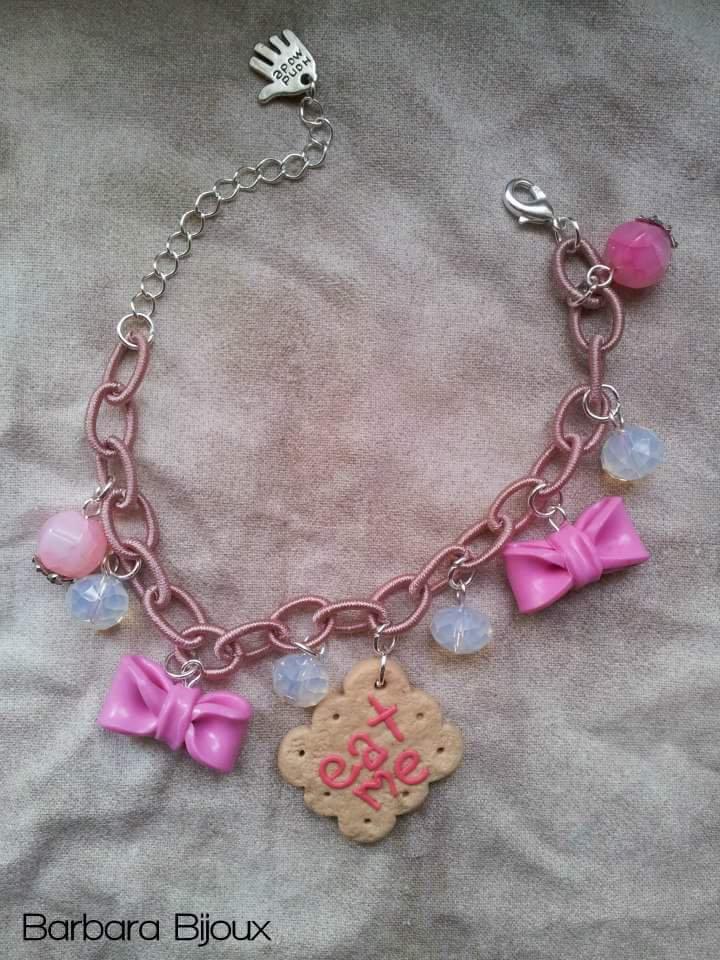 Bracciale fatto a mano ispirato ad Alice nel paese delle meraviglie con biscotto mangiami e fiocchetti rosa.