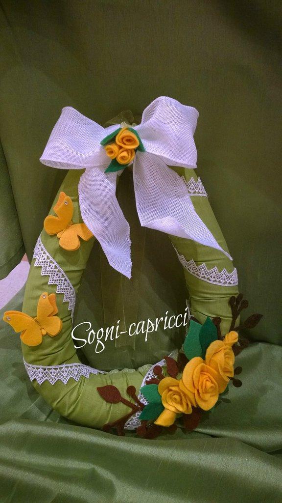 addobbo natalizio Ghirlanda dietro porta natalizia con rose gialle, farfalle e fiocco in sacco bianco