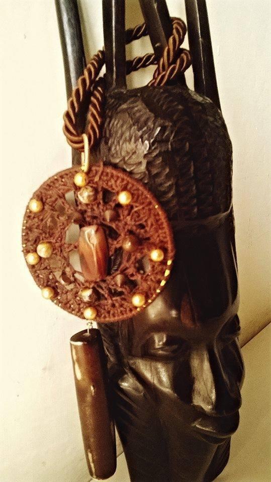 Collana con ciondolo di cotone marrone ,lavorata con il crochet con l'applicazione di decorazioni di legno e perline dorate.