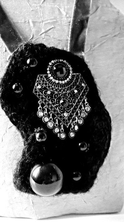 Collana con ciondolo di lana nero lavorata con il crochet .Vi è applicato un'orecchino una pallina nera e alcune perline nere (materiali di recupero).