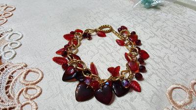 bracciale dorato con catena a maglie grandi e charms rossi