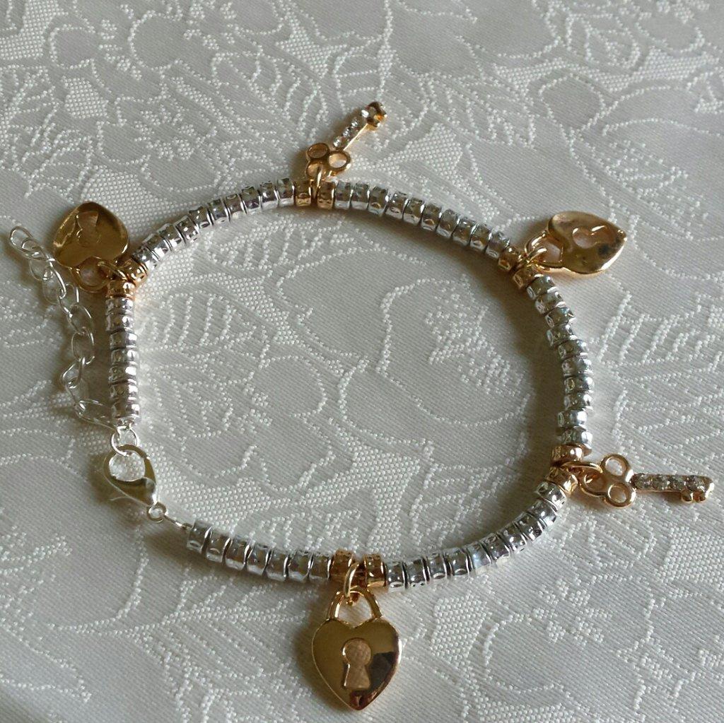Bracciale in metallo color argento con ciondoli chiavi e lucchetto