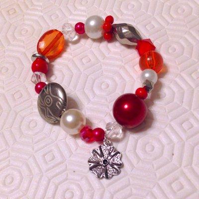 Braccialetto con perle e perline elastico nelle tonalità del rosso, bianco e argento con ciondolino a fiore, fatto a mano
