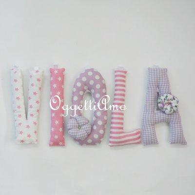 Viola: una ghirlanda di lettere in stoffa rosa e glicine per comporre il suo nome