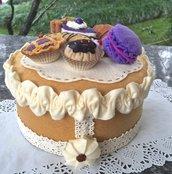Scatola di latta rivestita in feltro beige con fetta di torta e pasticcini