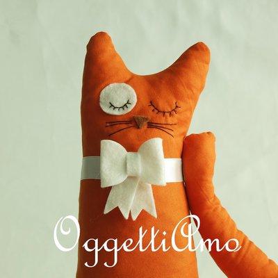 Un gatto arancione con fiocco bianco come fermaporta!