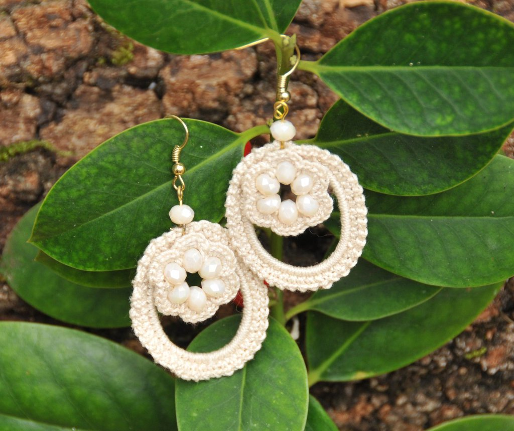 Orecchini ovali realizzati con filo di cotone e perline di un tenue color panna.