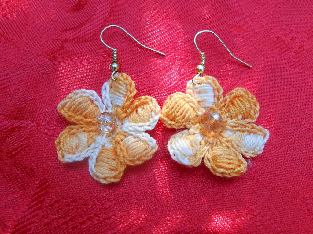 Orecchino a forma di fiore, con sei petali ed una perlina centrale, realizzato con filo di cotone color arancio.