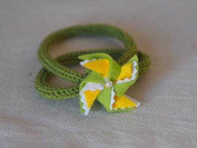 Bracciale a due fili(toni:verde,giallo e bianco).Maglia in lana tubolare e motivo in feltro e perla con girandola.Fatto a mano.Personalizzabile.Gioiello/accessorio.Aria di primavera