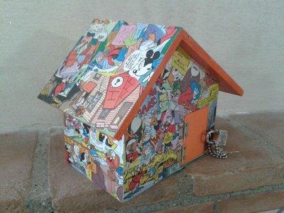 """Salvadanaio """"Topolino"""" a forma di casetta decorato con fumetti, bordi e porta arancioni"""