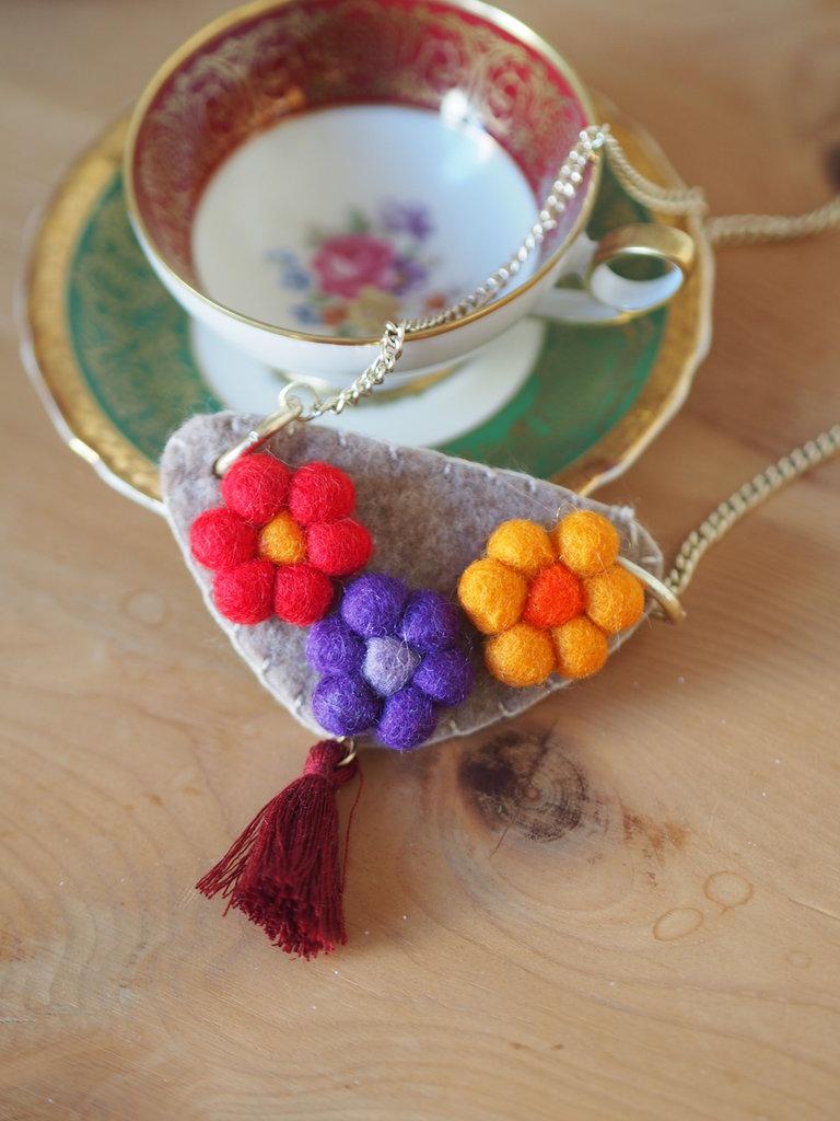 Collana con motivo centrale in feltro,fiori e nappina.Catena dorata con triangolo in feltro e 3margherite.Nappina centrale