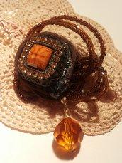 Spilla fatta a mano con cabochon in metallo brunito e piccoli strass color ambra adagiata su un fiore con petali composti di tre fili di corallini marroni e con piccolo ciondolo