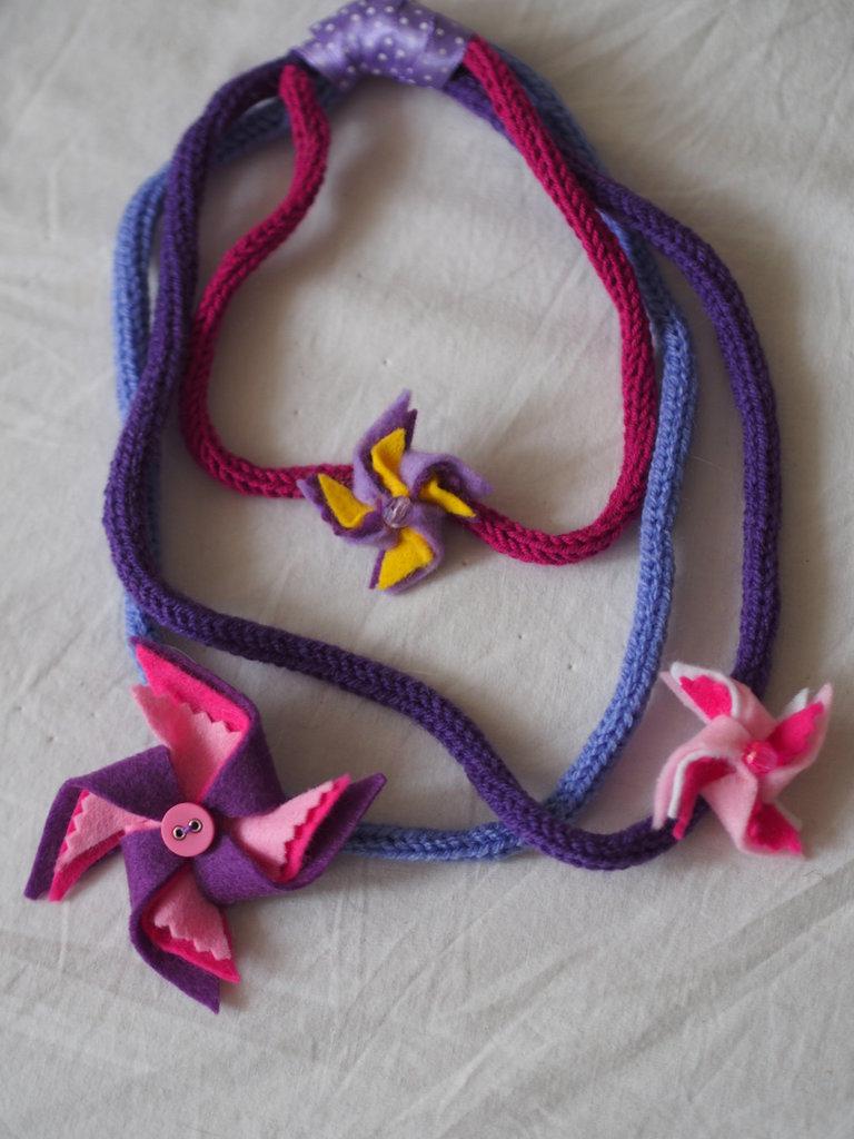 Collana in maglia tubolare (tricotin).3 FILI scalari.3 colori (viola,ciclamino,lilla).3 Girandole in feltro colorato con perle.Rifinita con nastro in raso.