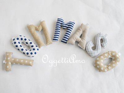 Tommaso: una ghirlanda di lettere di stoffa imbottita per comporre il suo nome in blu e beige