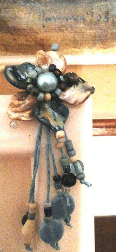 spilla fatta a mano con fiore a 5 petali in madreperla turchese e marrone chiaro con perla turchese al centro e cascata di corallini nelle stesse sfumature del fiore