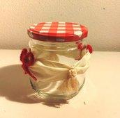 Piccolo barattolo per marmellate e composte con coperchio a quadretti bianco e rosso decorato con fiocchetti rossi lavorati all'uncinetto e nappine