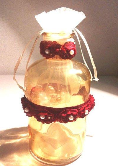 Bottiglietta in vetro fumè color ambra decorata a mano con roselline rosso scuo assemblate e cucite su un nastro in tulle con una piccola perla al centro di ognuna