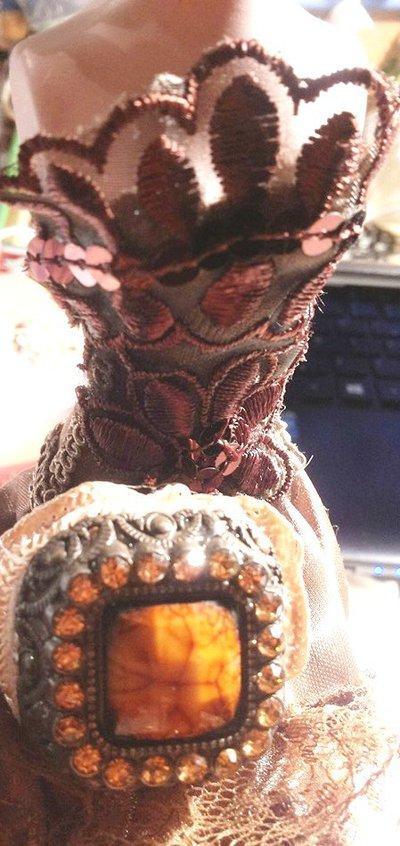 anello grande quadrato in metallo color bronzo con cabochon in pietra sintetica color ambra contornato alla base con tessuto elastico ecrù