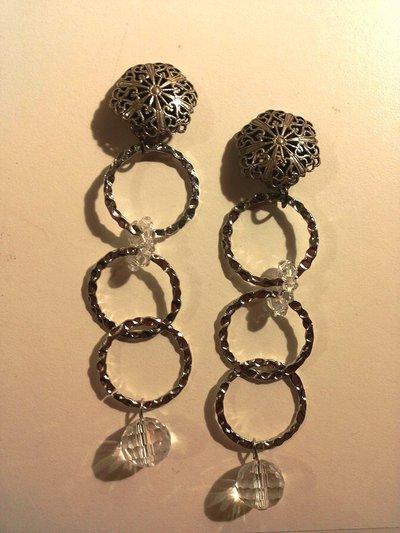 Orecchini in metallo color argento con bottone con clip lavorato tipo filigrana e pendente formato da 3 anelli in metallo argento