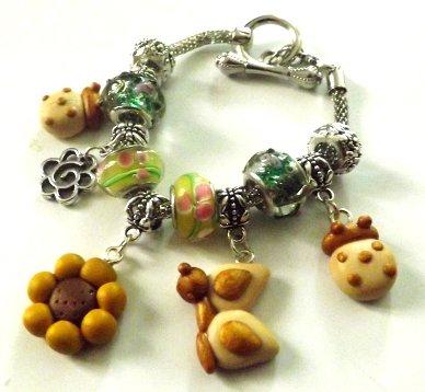Bracciale con perle a foro largo,base snake,ciondoli in fimo girasole,farfalla e coccinella idea regalo per lei